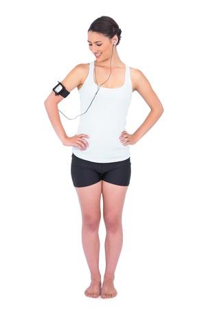 armband: Sorridente modello snello indossando la fascia tenere il lettore mp3 mentre posa su sfondo bianco