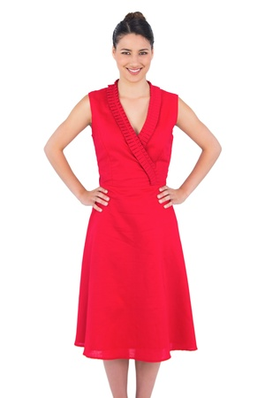 Smiling elegant brunette in red dress posing on white background photo