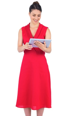 Content elegant brunette in red dress on white background holding tablet pc photo