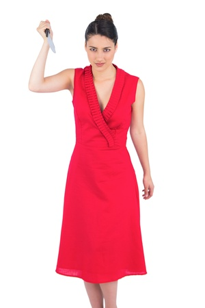 Frightening elegant brunette in red dress on white background holding knife photo