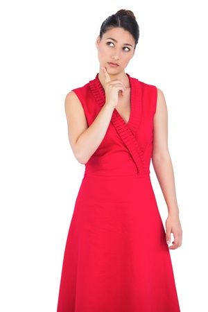 Thoughtful elegant brunette in red dress posing on white background photo