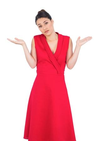 hesitant: Hesitant elegant brunette in red dress posing on white background
