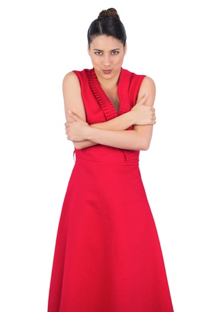 Glamorous young model in red dress on white background being cold photo