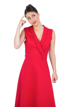Thoughtful glamorous model in red dress posing on white background photo