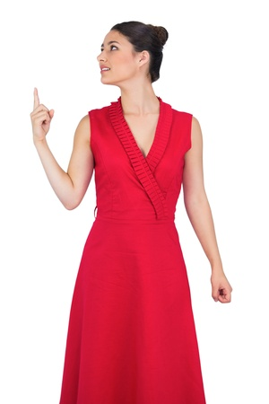 Cheerful glamorous model in red dress on white background pointing up photo