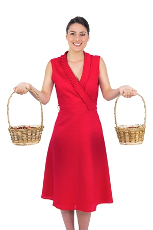 Cheerful glamorous model in red dress on white background holding baskets photo