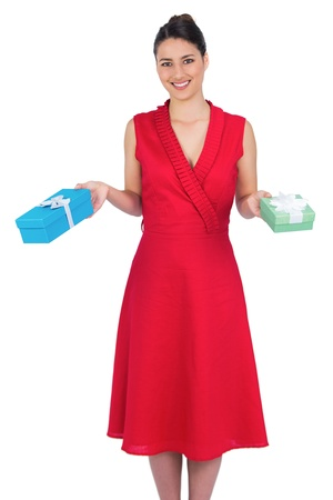 Smiling glamorous model in red dress on white background holding presents photo