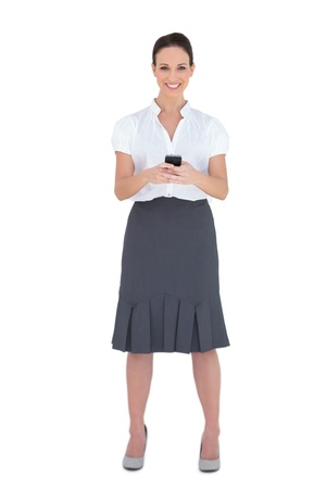 Smiling businesswoman sending a text message while posing on white background  photo