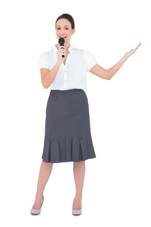 Energetic presenter holding microphone while posing on white background photo