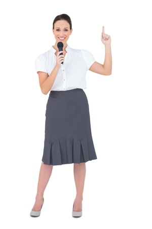 Smiling attractive presenter holding microphone while posing on white background photo