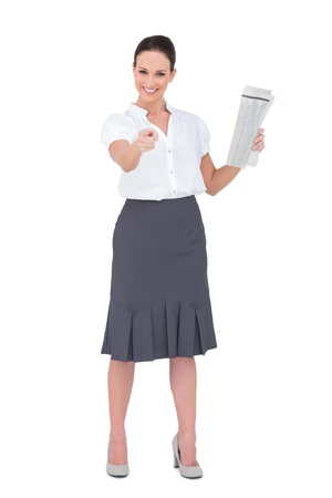 Stylish businesswoman pointing while holding newspaper on white background photo
