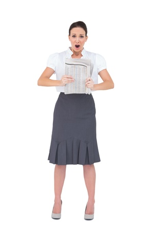 Shocked stylish businesswoman holding newspaper on white background