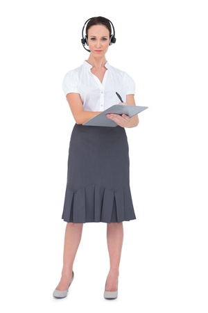 Pretty call center agent holding clipboard while posing on white background photo