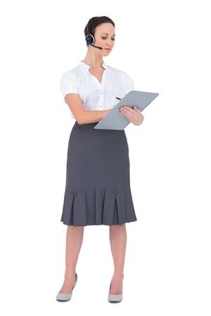 call center agent: Agente di call Focused centro possesso di appunti mentre posa su sfondo bianco