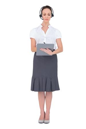 call center agent: Concentrato agente di call center che tiene appunti mentre posa su sfondo bianco