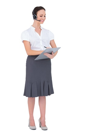 Peaceful call center agent holding clipboard while posing on white background photo