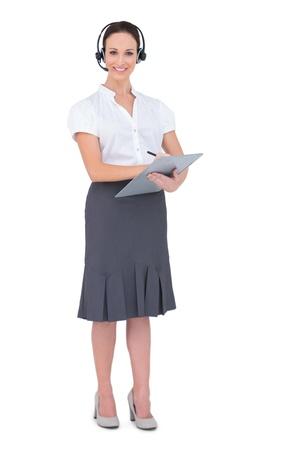 call center agent: Attraente agente di call center che tiene appunti mentre posa su sfondo bianco