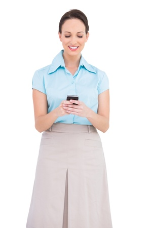Cheerful classy young businesswoman sending text message while posing on white background  photo