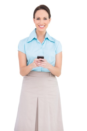 Happy classy young businesswoman sending text message while posing on white background