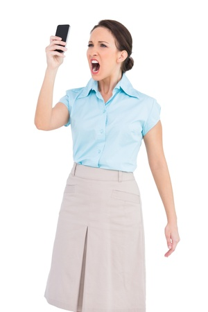 Angry classy businesswoman on white background shouting at her smartphone photo