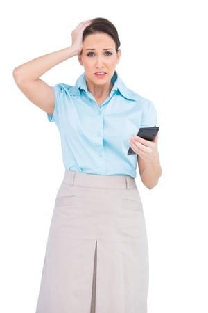 Worried classy businesswoman on white background holding calculator photo