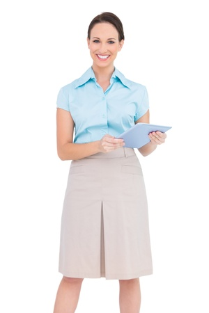 Happy young businesswoman holding tablet pc while posing on white background photo