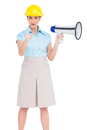 accusing: Stern attractive architect on white background pointing at camera while holding megaphone