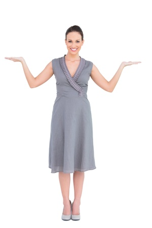 Cheerful elegant woman in classy dress posing on white background hands up photo