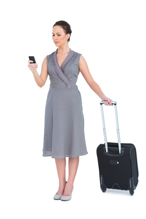 Serious gorgeous woman with her suitcase texting while posing on white background photo