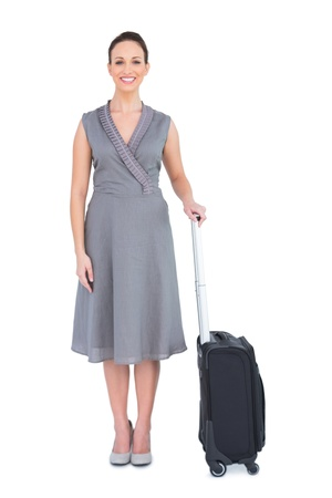Cheerful gorgeous woman with her suitcase posing on white background photo