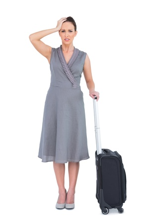 Worried gorgeous woman with suitcase posing on white background photo