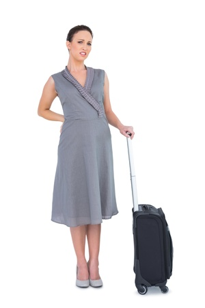 Gorgeous woman with suitcase suffering from painful back while posing on white background photo