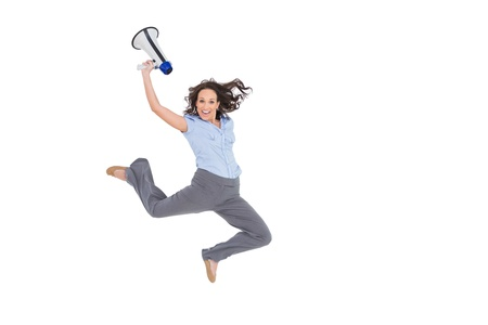 Cheerful classy businesswoman on white background jumping while holding megaphone photo