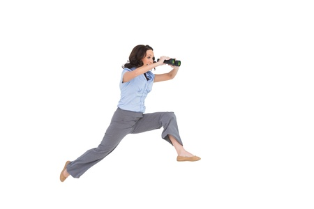 Cheerful classy businesswoman on white background jumping while holding binoculars photo