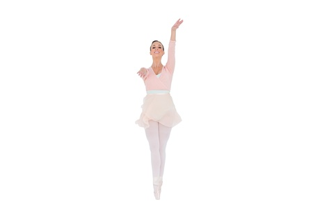 en pointe: Smiling ballerina with her arms extended on white background