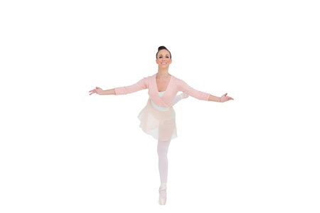 en pointe: Smiling gorgeous ballerina standing in a pose on white background  Stock Photo