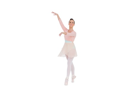 en pointe: Smiling gorgeous ballerina with her arms up posing on white background