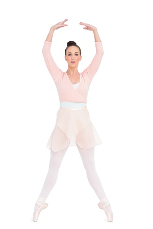 en pointe: Focused attractive ballerina standing on her tiptoes on white background