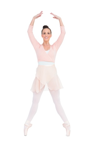 tiptoes: Smiling attractive ballerina standing on her tiptoes on white background  Stock Photo