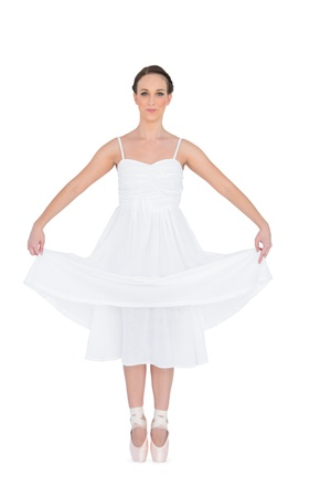 Peaceful young ballet dancer standing on her tiptoes on white background  photo