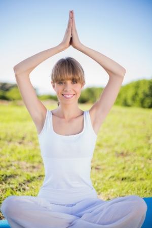Happy natural young woman doing yoga outside in a sunny meadow photo