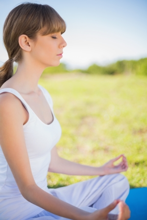 Young woman meditating in lotus position outside in a sunny meadow photo
