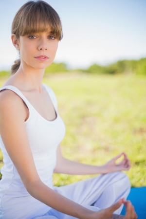 Serious young woman meditating in lotus position outside in a sunny meadow photo