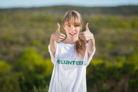 altruism: Rubia natural con una camisa t voluntario hasta que los pulgares a la cámara