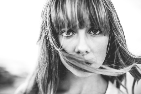 Hipster girl with fringe staring at camera in black and white artistic shot photo