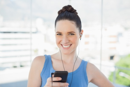 mpg: Attractive slender woman listening to music while exercising in bright sports hall