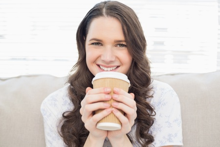 Smiling pretty woman in pyjamas having coffee sitting on cosy sofa photo
