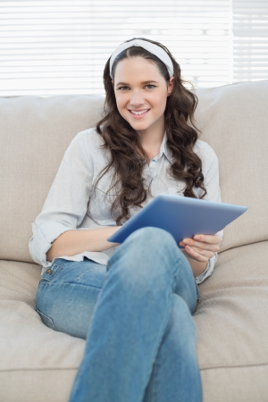 Cheerful casual woman on cosy couch in bright living room using tablet pc photo