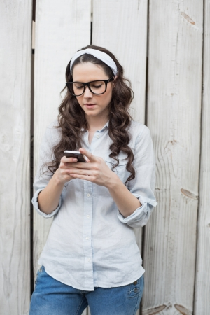 Trendy woman with stylish glasses sending text message while posing on wooden background photo