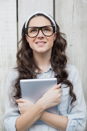 Pensive trendy woman with stylish glasses holding her tablet posing on wooden background photo